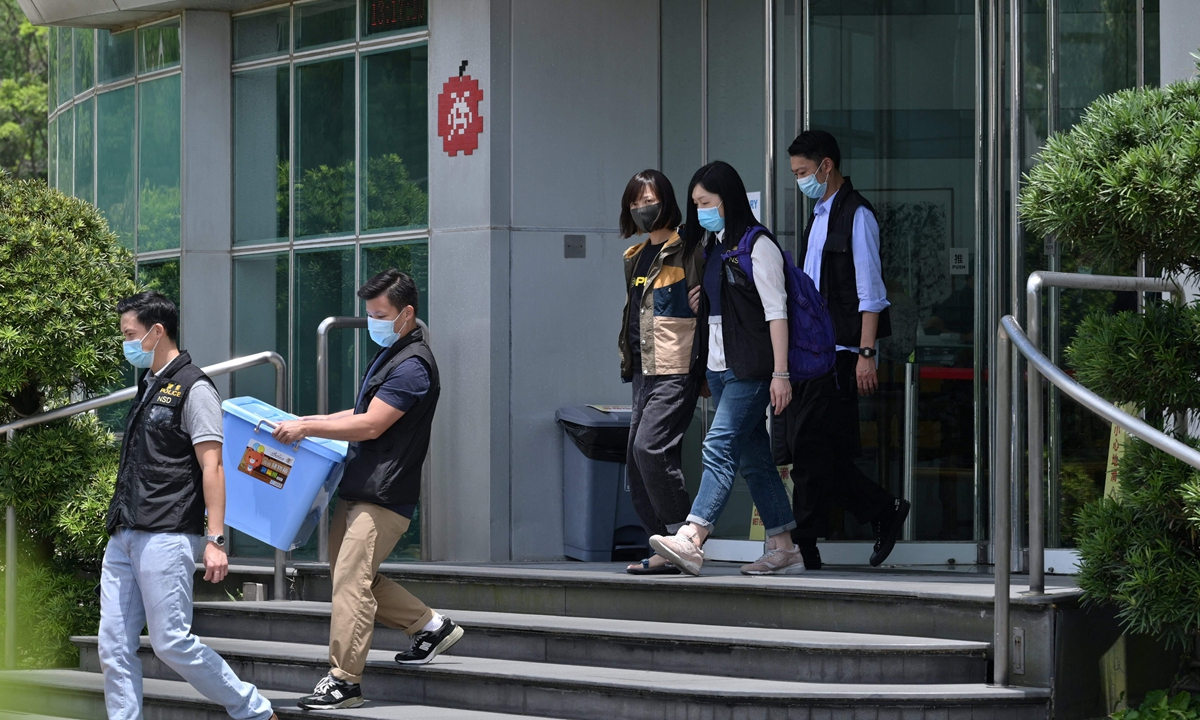 Police escort deputy chief editor Chan Puiman (center) from the Apple Daily newspaper offices in Hong Kong on Thursday. Photo: VCG