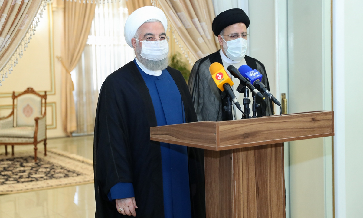 Iranian President Hassan Rouhani (left) and President-elect Ebrahim Raisi speak to press members during their meeting in Tehran, Iran on Saturday. Photo: AFP