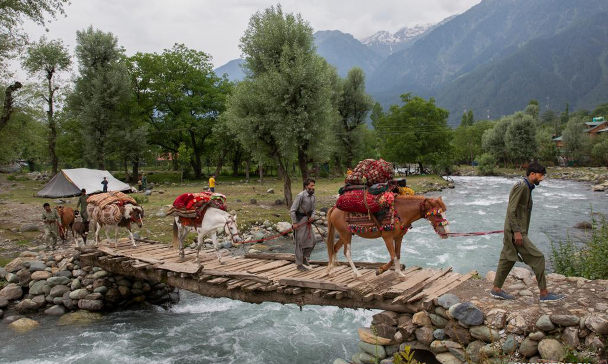 Nomads cross a bridge with horses in Pahalgam village, about 90 km south of Srinagar city, the summer capital of Indian-controlled Kashmir, June 20, 2021. The nomadic tribe known as Bakerwals has begun the seasonal migration towards upper reaches of Indian-controlled Kashmir in the wake of the rising temperatures in plains. (Xinhua/Javed Dar)