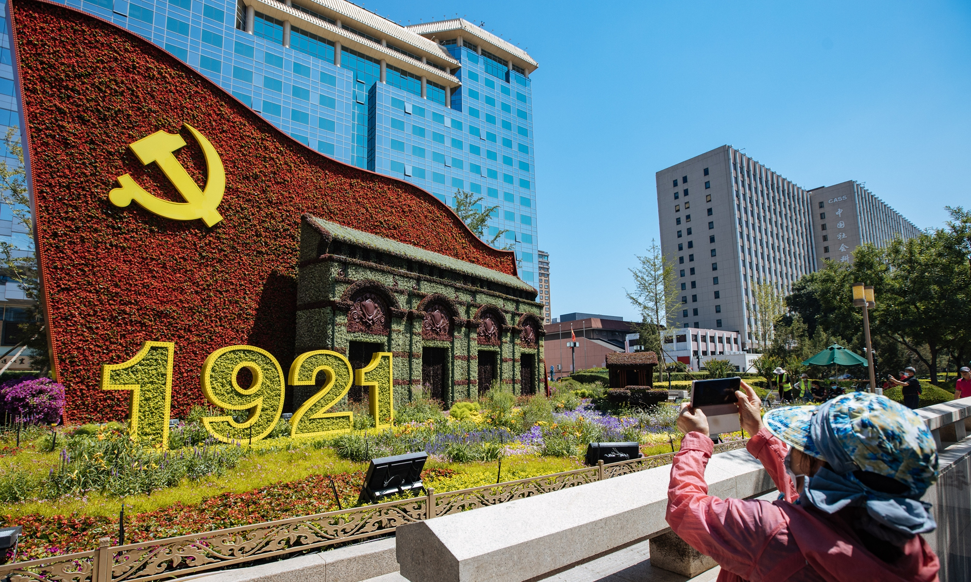 A visitor takes a photo of a floral decoration that has been put up along the Chang'an Avenue in Beijing to celebrate the 100th anniversary of the founding of the Communist Party of China (CPC) on Monday.  Under the theme of Remain true to its original aspiration, keep its mission firmly in mind,
