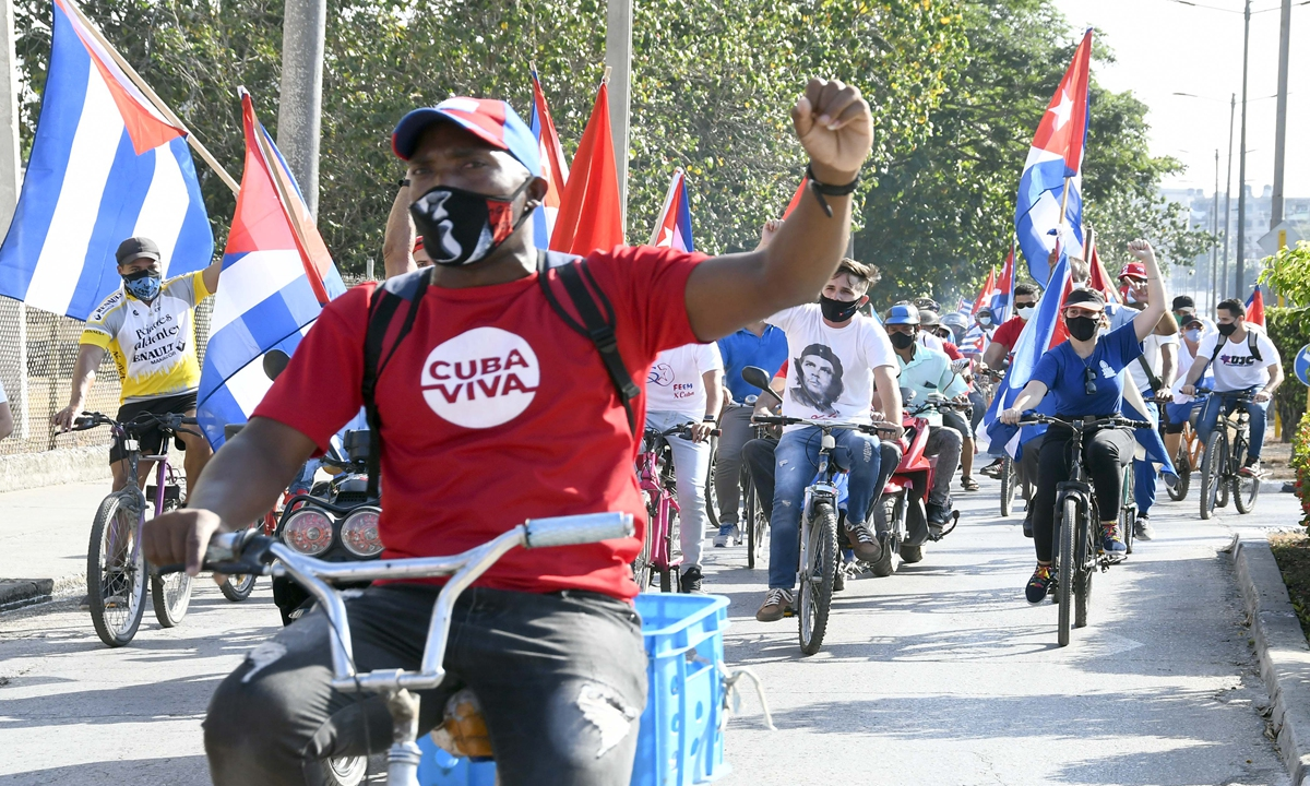 Local residents ride bicycles to protest the nearly 60-year US embargo against Cuba in SantaClara,Cubaon April 25. Photo: Xinhua