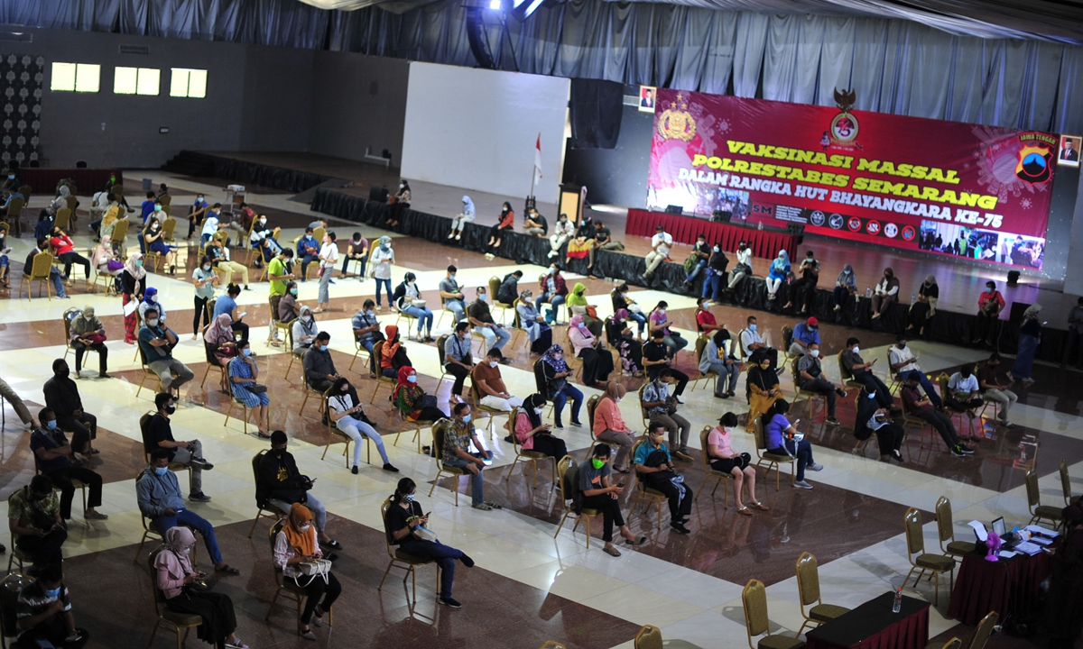 Residents gather to get vaccinated with the Sinovac vaccine against the COVID-19 coronavirus during a mass vaccination drive, in Semarang on Tuesday, as infections soar in Indonesia. Photo: AFP