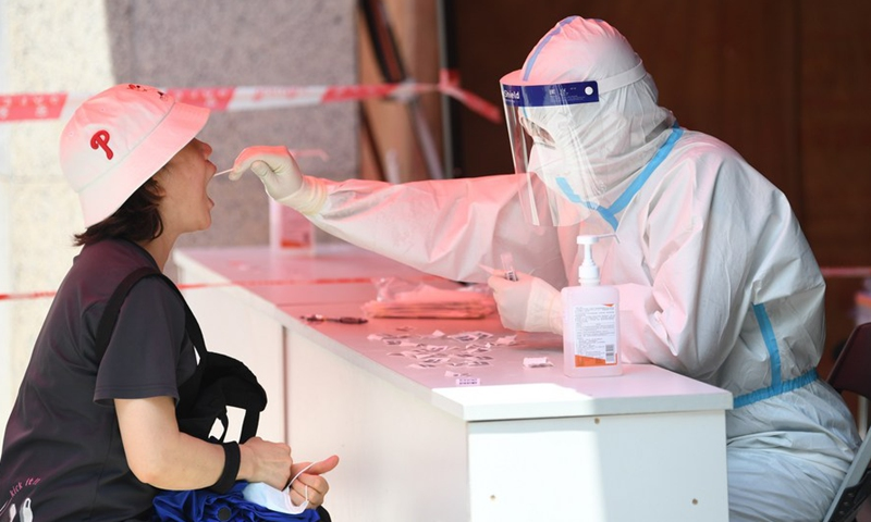 A medical worker collects swab samples from a resident for COVID-19 nucleic acid test in Liwan District of Guangzhou, south China's Guangdong Province, May 27, 2021. Photo:Xinhua
