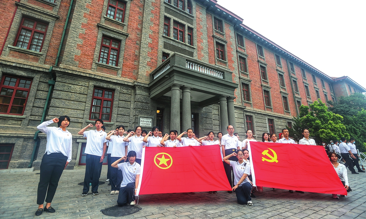 Students carrying a CPC flag (right) and a flag of the Communist Youth League of China have a group photo taken in front of the Red Building on Tuesday. Photo: Cui Meng/GT