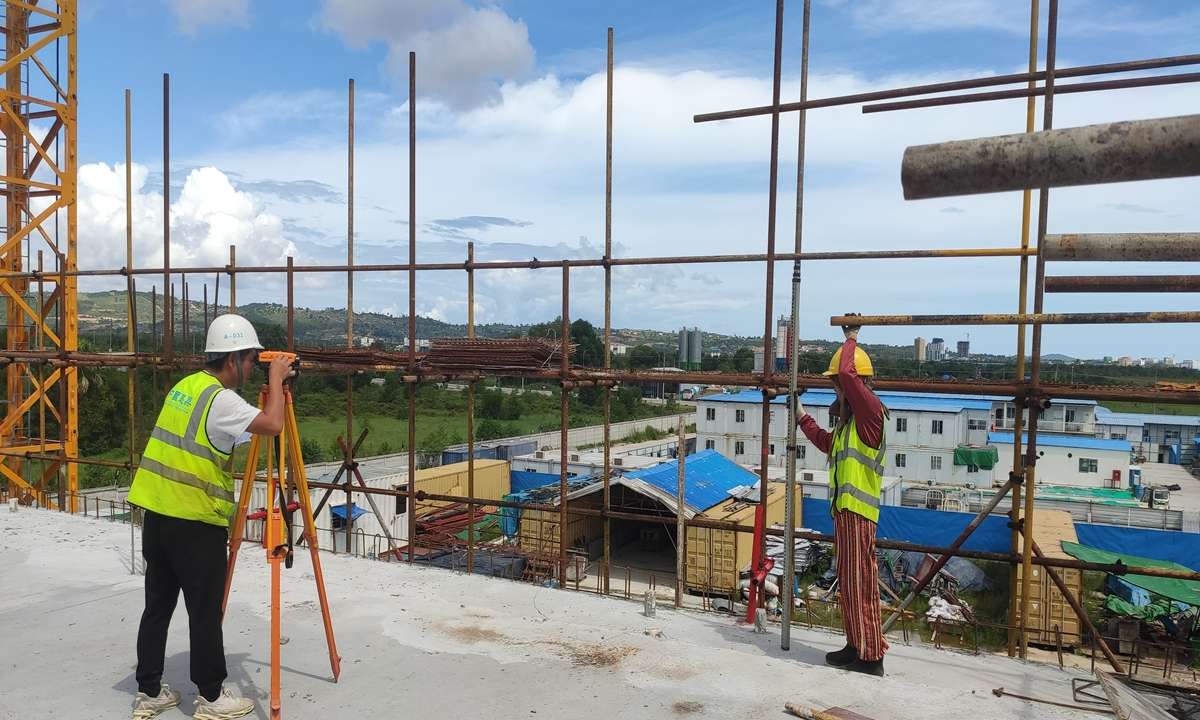 An engineer measures the height and level of a building with the help of a colleague on Monday. Photo: Courtesy of CSCEC