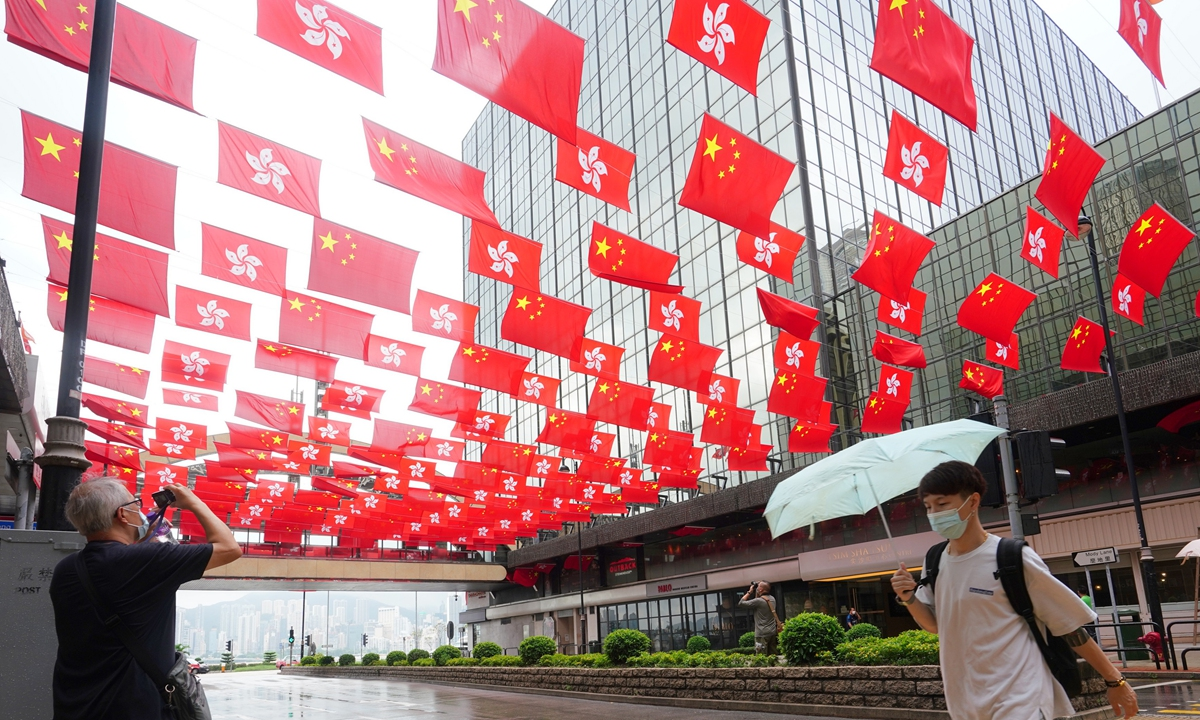 Local residents take photos of more than 200 Chinese national flags and flags of Hong Kong Special Administrative Region along Mody Road, Tsim Sha Tsui in Hong Kong on Tuesday, ahead of July 1 which marks the Communist Party of China's centenary and the 24th anniversary of Hong Kong's return to the motherland. Photo: cnsphoto