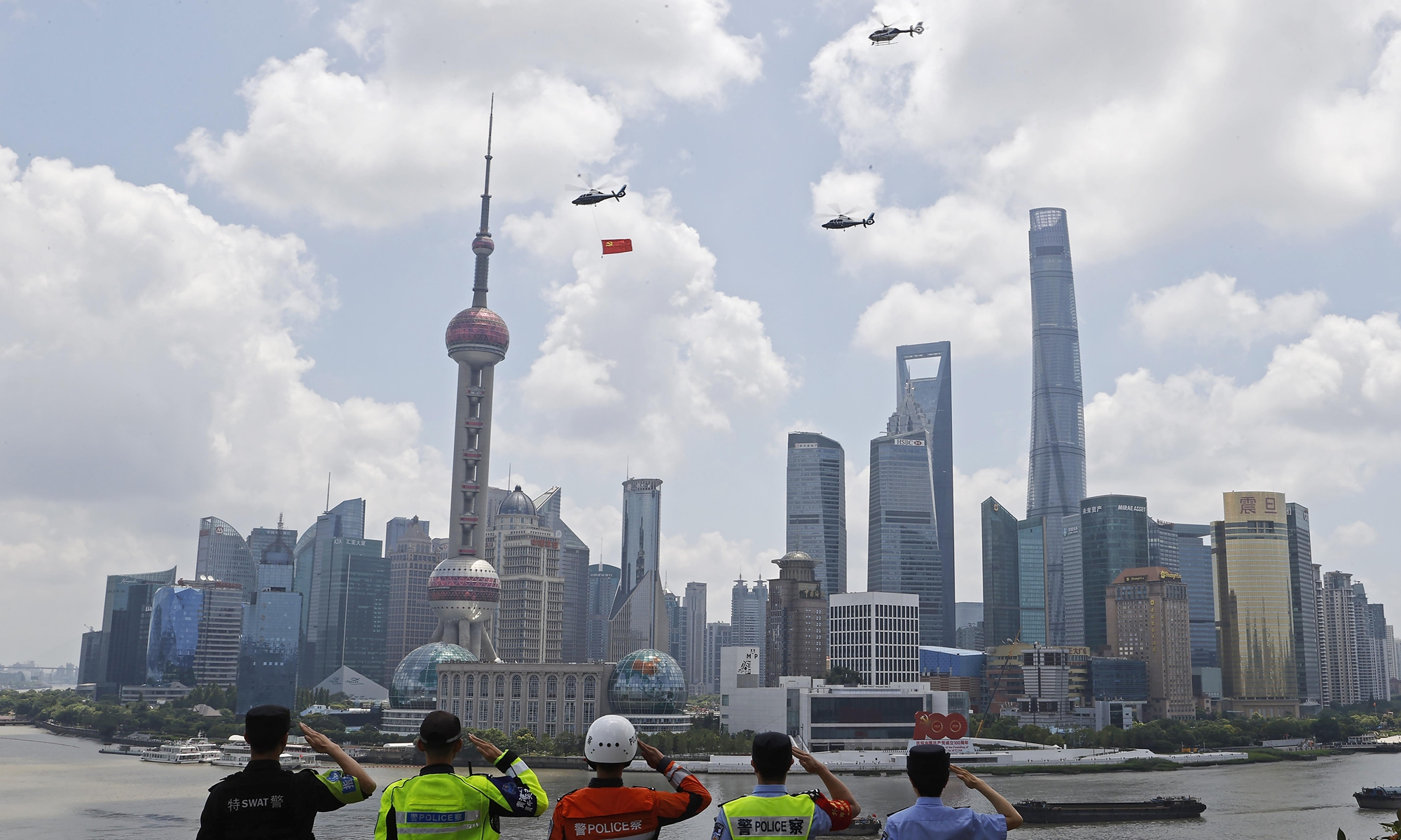 Three police helicopters of the Shanghai Public Security Bureau fly a Party flag over the Huangpu River to celebrate the CPC's centennial in Shanghai on Thursday. Photo: cnsphoto