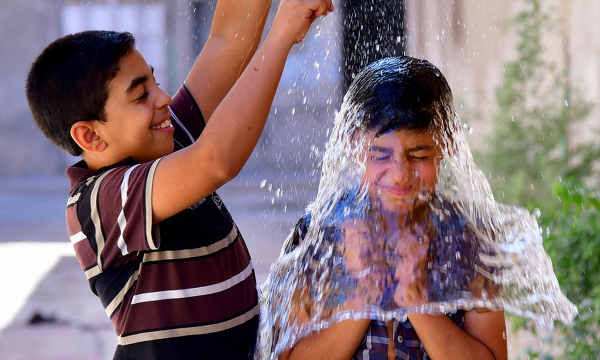 Syrian children cool off with water during hot weather in Damascus, Syria, on June 29, 2021. (Photo by Ammar Safarjalani/Xinhua)