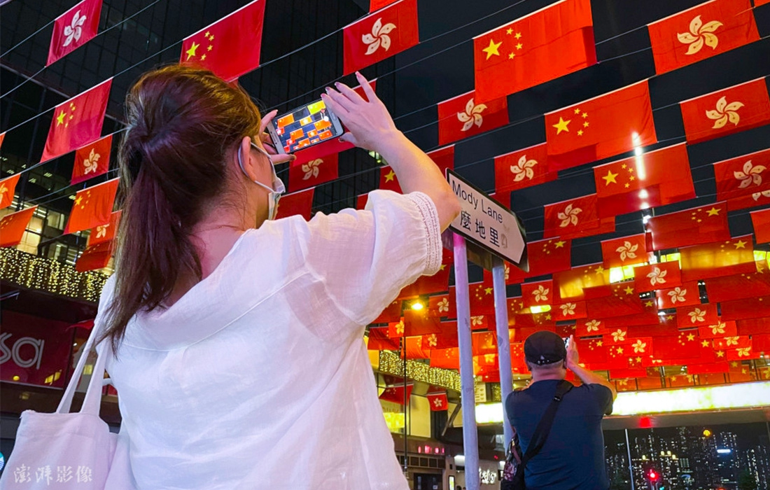 A woman takes photos of the China's national flags and the flags of the Hong Kong Special Administrative Region in Tsim Sha Tsui, Hong Kong, on June 29. Photo: Pengpai