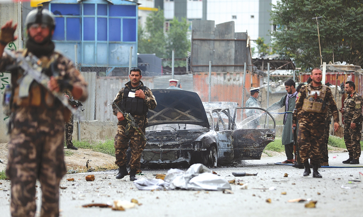 Security personnel inspect a damaged vehicle which was firing rockets in Kabul, Afghanistan on Tuesday. At least three rockets hit near the presidential palace shortly before Afghan President Ashraf Ghani was to give an address to mark the Muslim holiday of Eid-a-Adha.  Photo: VCG