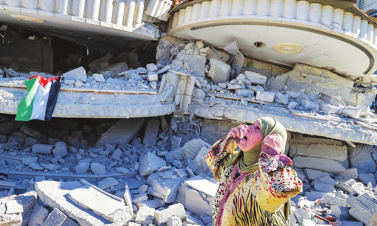 A Palestinian woman reacts outside a building that belonged to Montasser Shalabi, who was arrested in May on suspicion of carrying out a drive-by shooting attack on an Israeli student, after it was demolished by Israeli forces in the village of Turmus'ayya near Ramallah in the occupied West Bank on Thursday. Photo: AFP