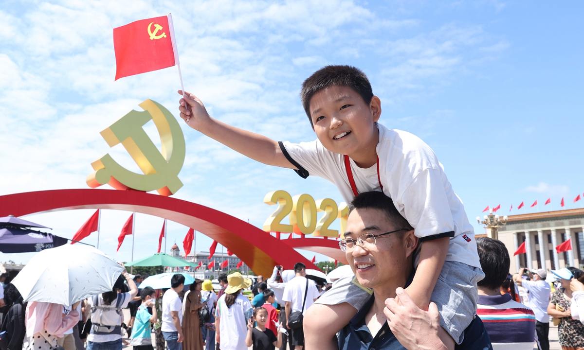 A child waves a flag of the CPC at Tian'anmen Square on Saturday. Photo: IC