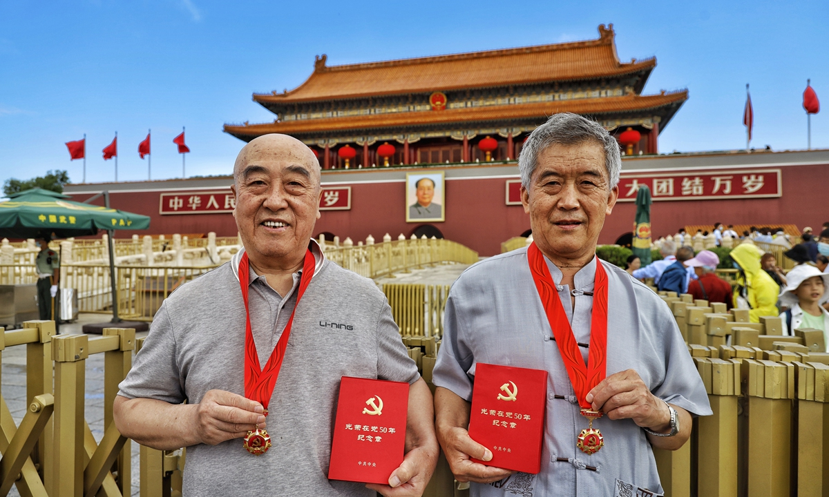 Two men have a photo taken in front of the Tian'anmen Rostrum wearing emblems showcasing their membership to the CPC for more than 50 years. Photo: Li Hao/GT