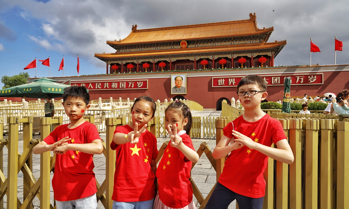 Four children in red pose in front of the Tian'anmen Rostrum on Saturday. Photo: Li Hao/GT