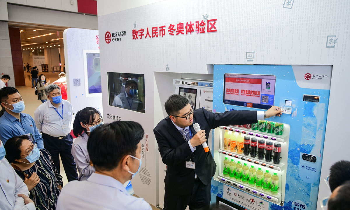 A staffer displays the digital yuan application scenarios to visitors in the World Intelligence Congress in Tianjin in May. Photo: cnsphoto
