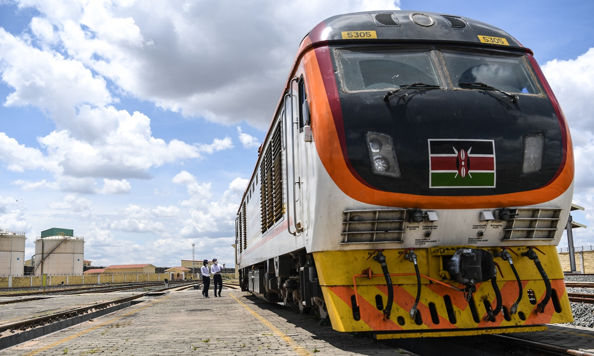 Employees walk along the Mombasa-Nairobi Railway in Nairobi on March 22. Photos: Xinhua