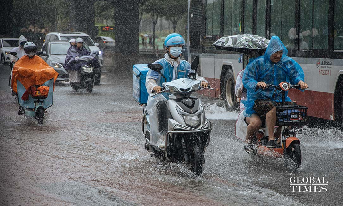 Beijing residents ride forward in heavy rain, experiencing a less busy rush hour on Monday morning as many companies asked employees to work from home or cancel the clock in. Photo: GT/Li Hao