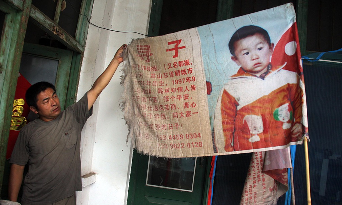 Guo Gangtang shows the information of his abducted son on August 8, 2010. Photo: CFP