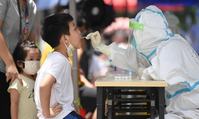 A medical worker in protective suit collects a swab sample from a boy for COVID-19 nucleic acid testing in the subdistrict of Baihedong in Liwan District of Guangzhou, south China's Guangdong Province, June 12, 2021. (Photo:Xinhua)