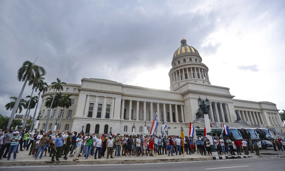 Cubans hold their country's flag to support Cuban President Miguel Díaz-Canel in front of the National Capitol building in Havana on Monday amid anti-government protests that were believed to be a US-backed
