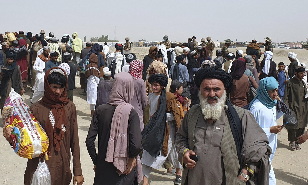 Pakistani soldiers guard as stranded people gather near the Pakistan-Afghanistan border crossing following fighting between Afghan security forces and the Taliban in Pakistan on Friday. Photo: AP