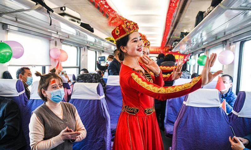 Staff members and passengers dance together in a passenger car of train No. K9756 from Korla to Yetimbulak in northwest China's Xinjiang Uygur Autonomous Region, Dec. 9, 2020.Photo:Xinhua
