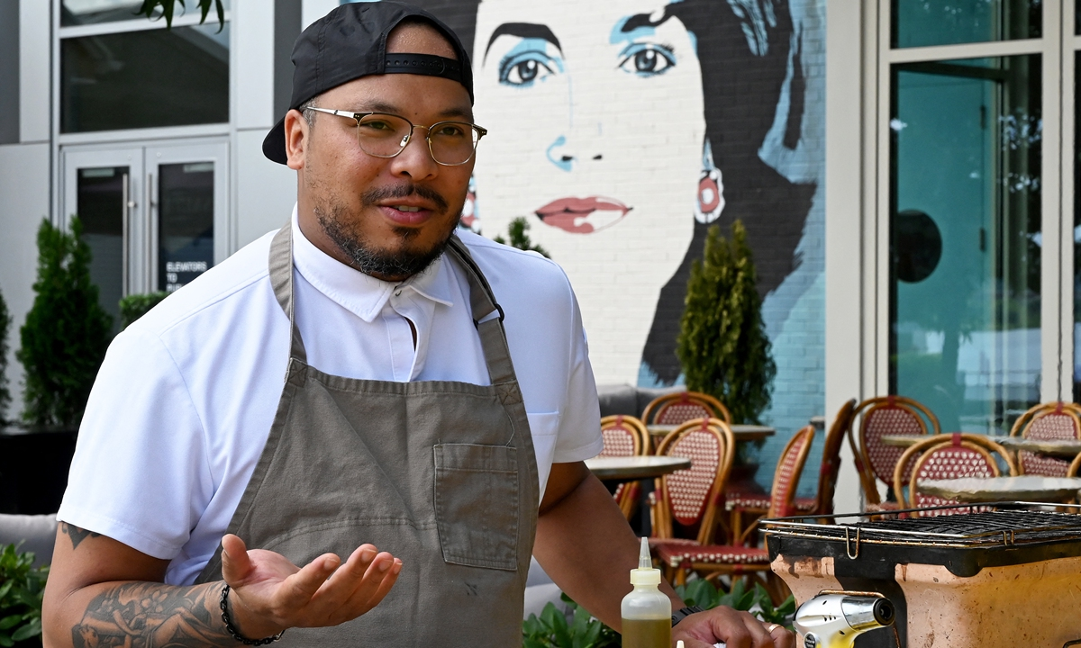 Jerome Grant  Top: Jerome Grant roasts sweet potatoes for a dish on June 25 in Washington DC. Photos: AFP