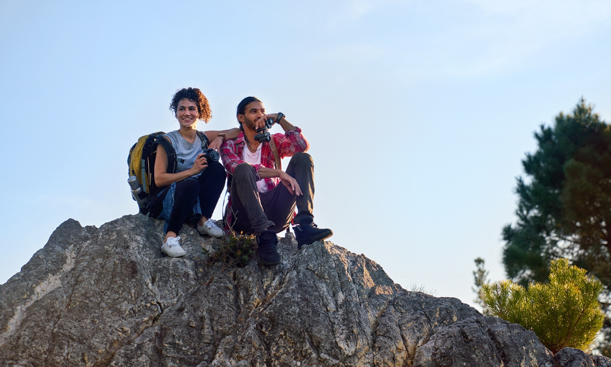 A happy young hiking couple relaxes on a rock. Photo: AFP