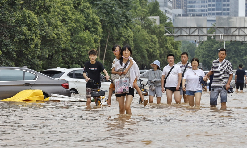 Residents wade through a flooded street in Zhengzhou, Central China's Henan Province on Tuesday. Photo: Li Hao/GT
