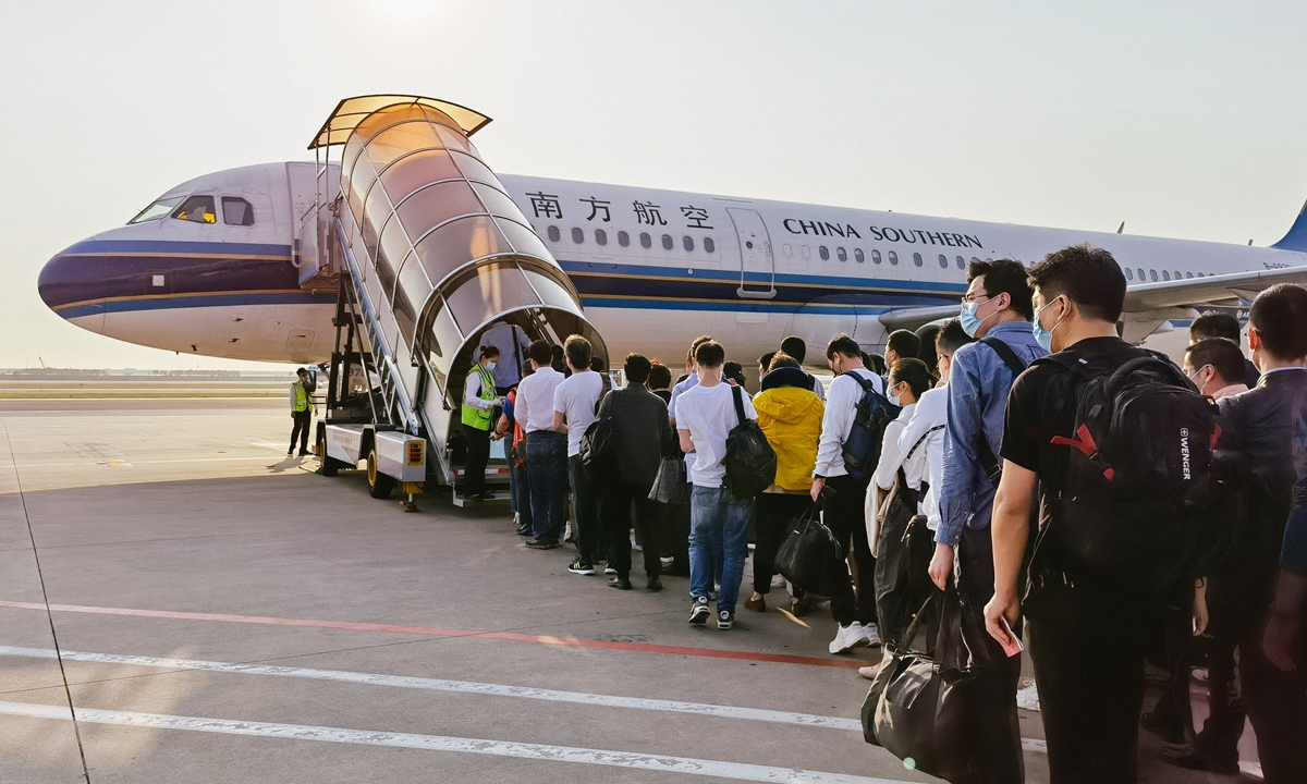 Travelers wait in queue to get on board a China Southern Airlines flight. Photo: VCG