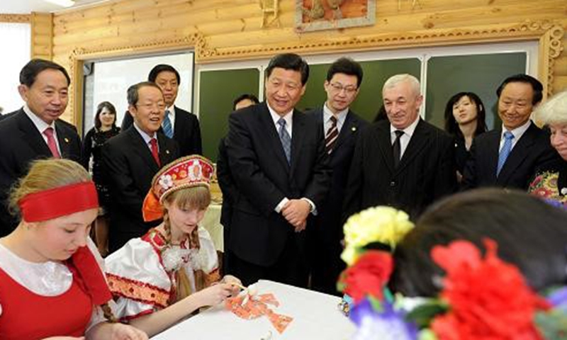 """Xi Jinping watches students making handicrafts in the All-Russian Children's Center """"Ocean,"""" March 2010."""