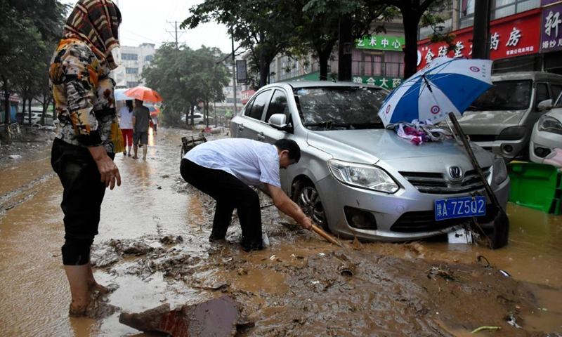 People clean up the silt around a trapped car in Mihe Town of Gongyi City, central China's Henan Province, July 21, 2021. Mihe Town suffered great damage due to the heavy rainfall on July 20, with a large number of roads damaged and vehicles flooded.(Photo: Xinhua)
