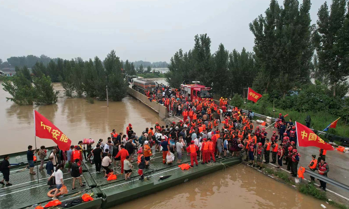 Rescue workers from China Anneng Group build a powered floatingbridgeto relocate flood-stricken residents in Xinxiang, Central China's Henan Province on Friday after rain-induced torrents threatened the city. Photo: VCG