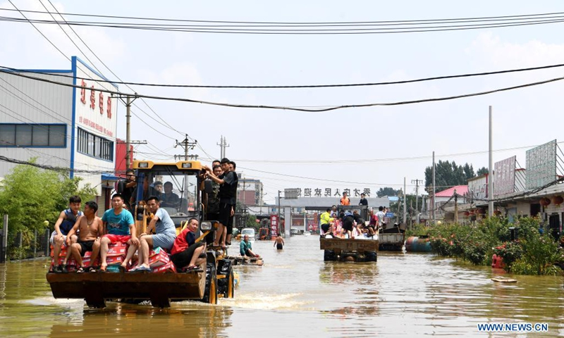 Stranded residents are evacuated on shovel loaders in flood-hit Xinxiang City, central China's Henan Province, July 24, 2021. (Photo: Xinhua)