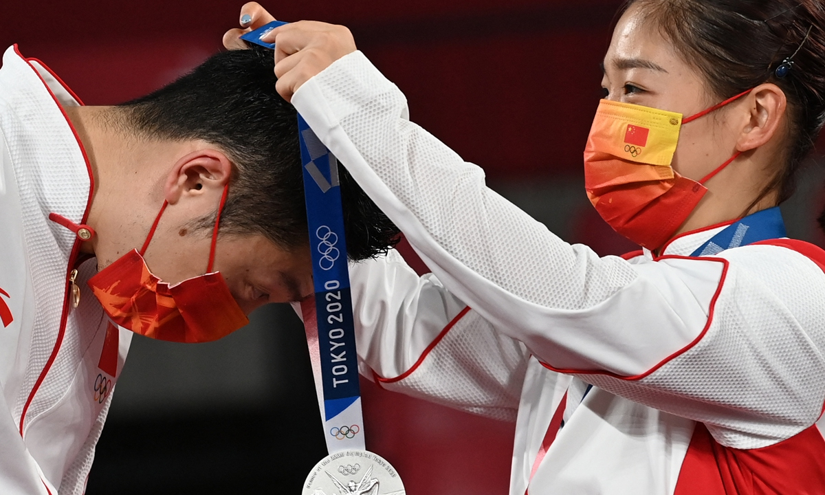 Xu Xin (left) receives his silver medal from teammate Liu Shiwen during the mixed doubles table tennis medal ceremony at the Tokyo Metropolitan Gymnasium during the Tokyo 2020 Olympic Games in Tokyo on Monday. Photo: AFP