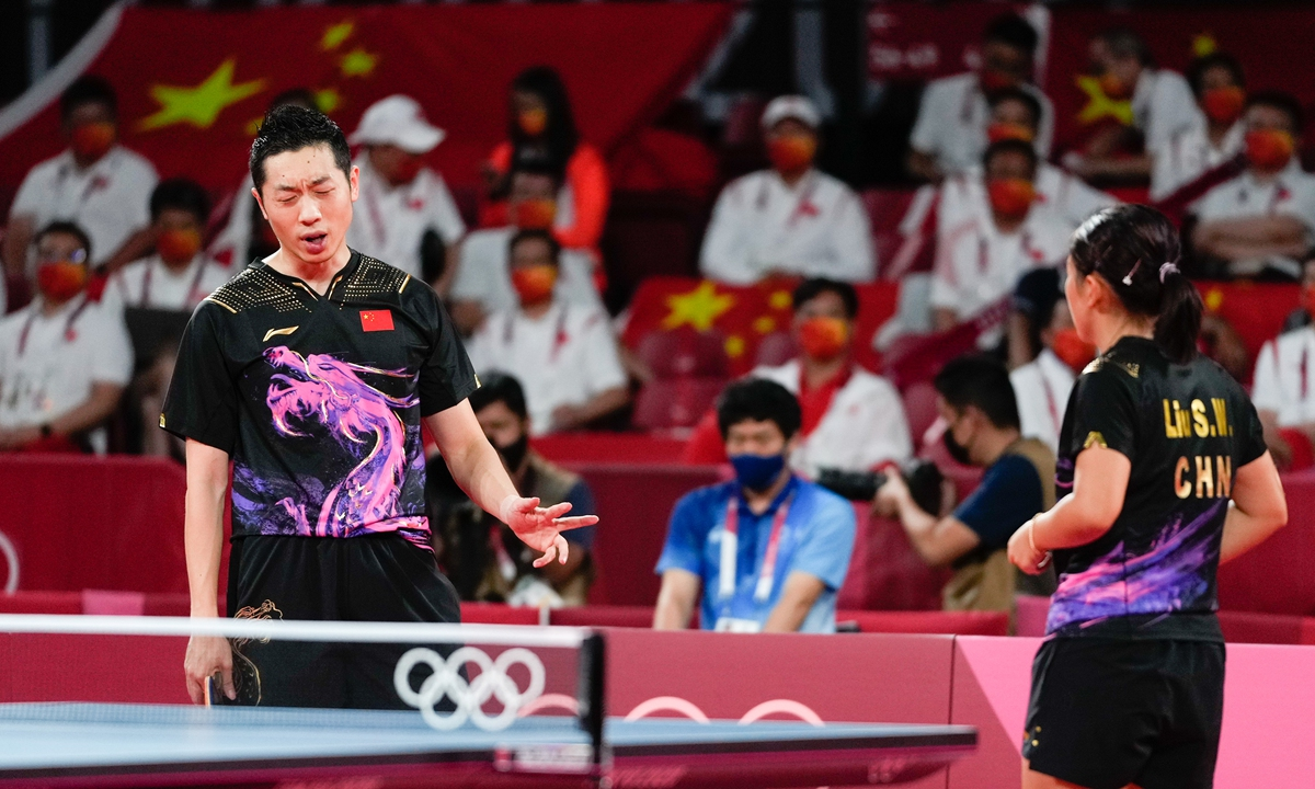 Chinese paddlers Xu Xin (left) and Liu Shiwen react during the match on Monday in Tokyo. Photo: VCG