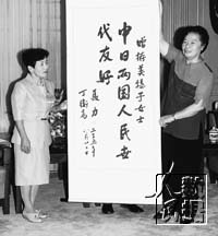 Nie Li (right) presents Kato Mihoko a calligraphic work.