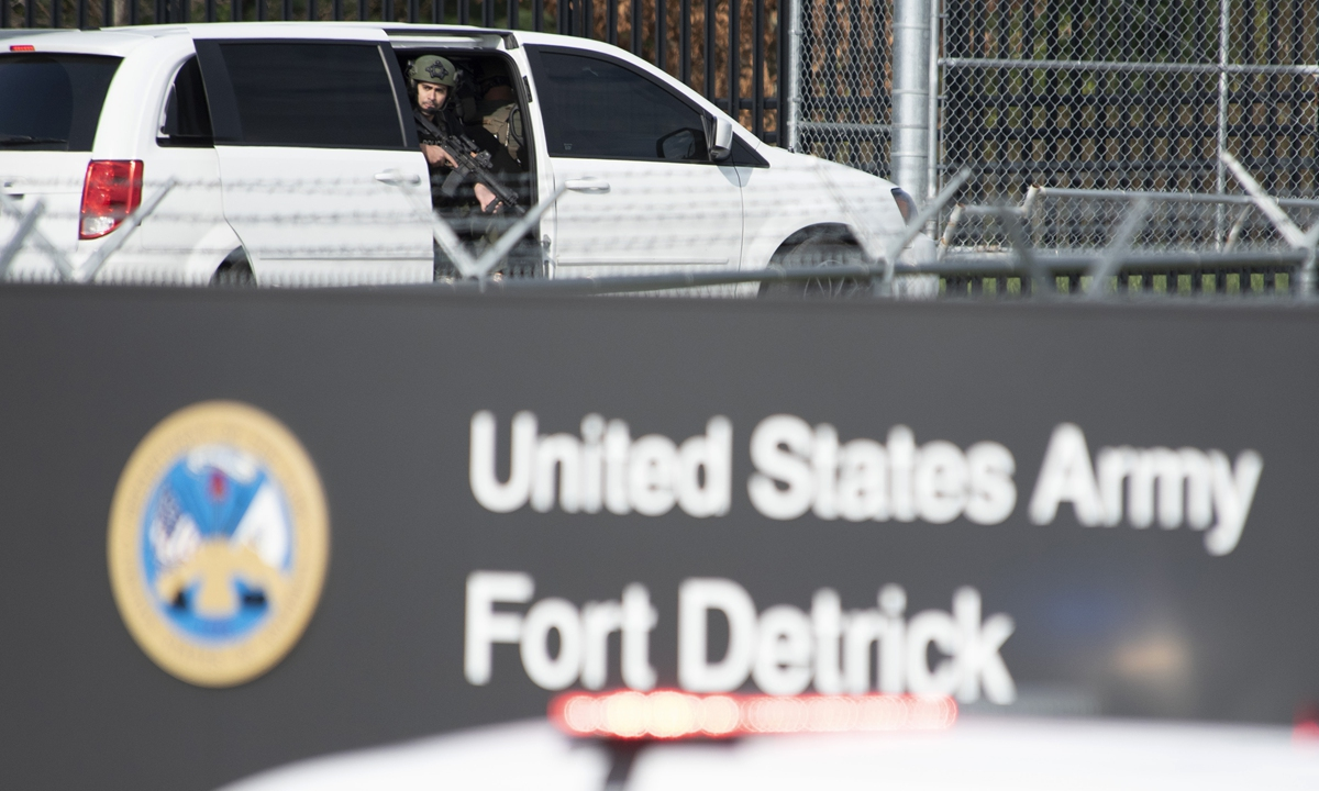 A member of the Frederick Police Department Special Response Team peers out of a minivan before the team entered Fort Detrick on April 6. Photo: VCG