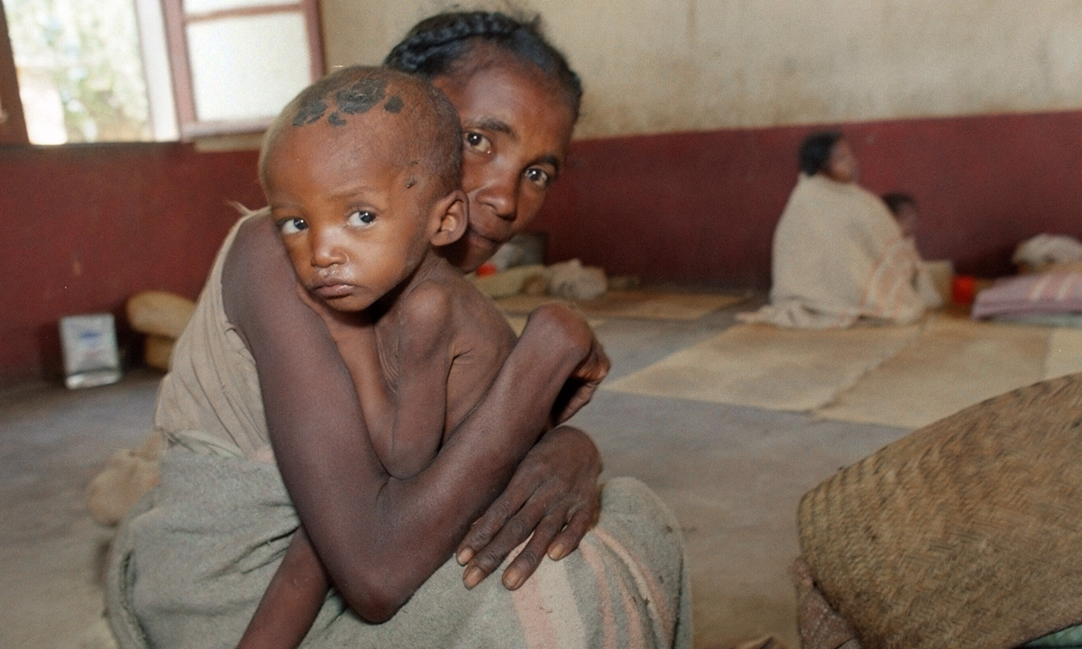 A woman holds her malnourished child as they wait for food at a feeding center in Fort Dauphin, south of Madagascar. Photo: AFP