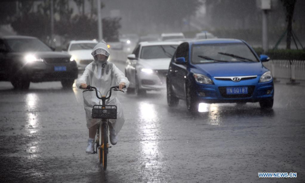 A citizen rides a bike in rain on a street in Haidian District of Beijing, capital of China, July 12, 2021. Photo: Xinhua