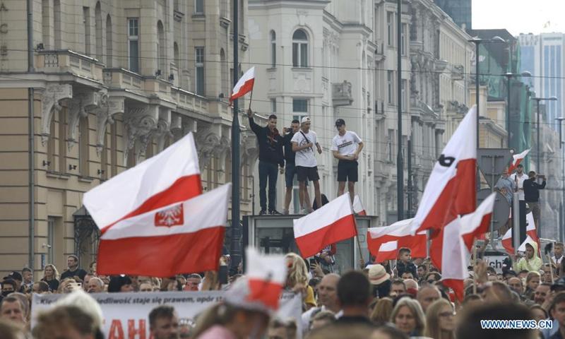 Ludzie zebrali się na pamiątkę Powstania Warszawskiego 1 sierpnia 2021 r. w Warszawie.  1 sierpnia 1944 r. polskie podziemie kierowane przez Armię Krajową rozpoczęło wielką operację wojskową, mającą na celu wyzwolenie Warszawy spod okupacji hitlerowskiej.  Powstanie, które trwało 63 dni, było największą operacją militarną jakiegokolwiek europejskiego ruchu oporu przeciwko nazistowskim Niemcom.  (Zdjęcie: Job Arian / Xinhua)
