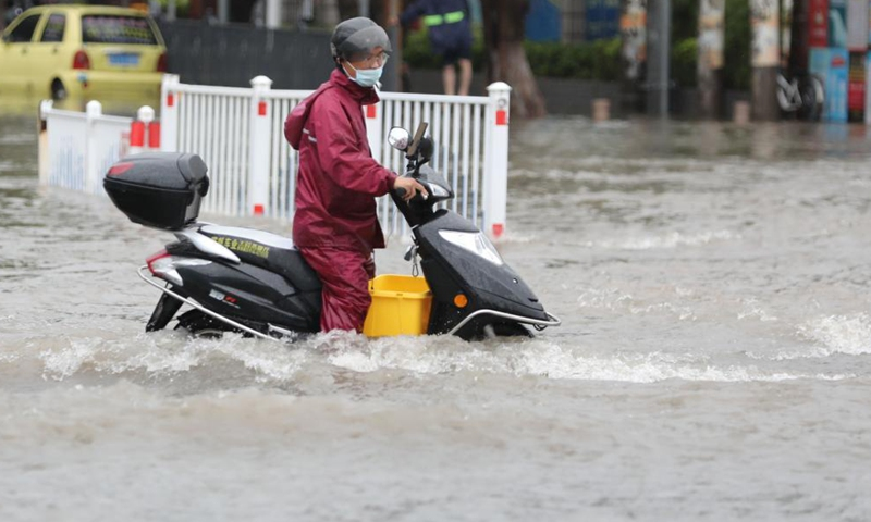 A citizen wades through a waterlogged road on a motorcycle in Jimei District of Xiamen, southeast China's Fujian Province, Aug. 5, 2021. Typhoon Lupit made its second landfall on Thursday in Fujian Province, bringing heavy downpours and forcing the evacuation of thousands. The local government has initiated an emergency response to flood and waterlogging amid torrential rains brought by Lupit.Photo:Xinhua