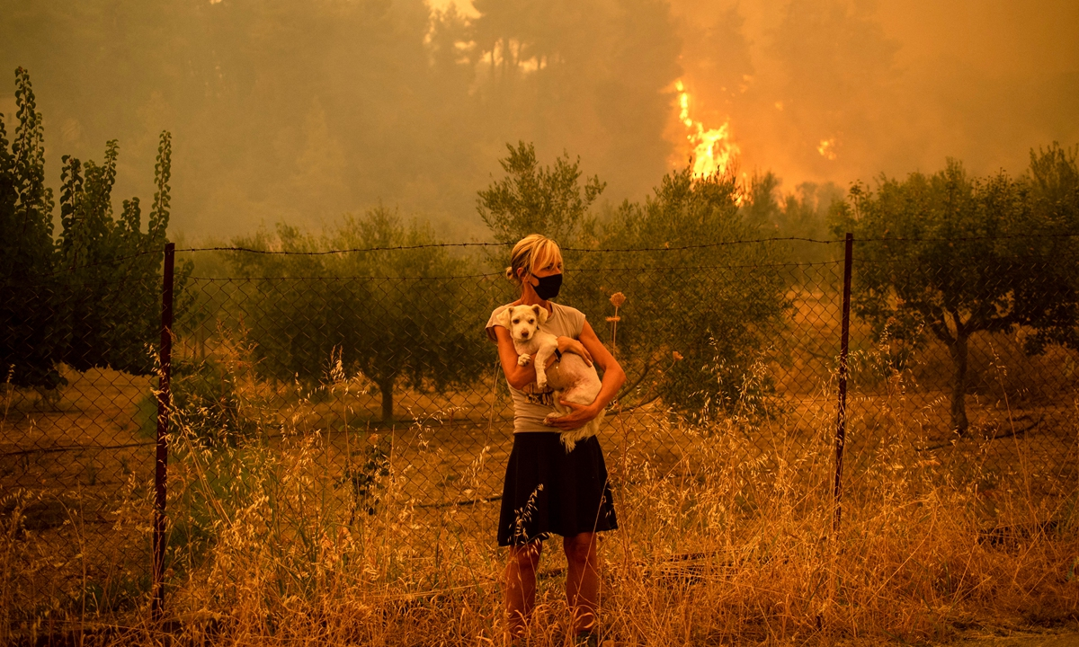 A woman holds a dog in her arms as forest fires approach the village of Pefki on Evia island, Greece on August 8. Greece and Turkey have been battling devastating fires for nearly two weeks as the region suffered its worst heatwave in decades, which experts have linked to climate change. Photo: AFP