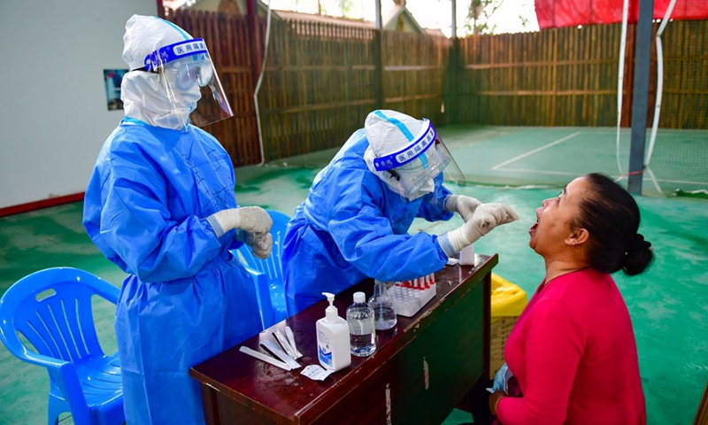 A medical worker takes a swab sample from a woman for COVID-19 testing at a testing site in Ruili City, Southwest China's Yunnan Province, April 6, 2021.(Photo: Xinhua)
