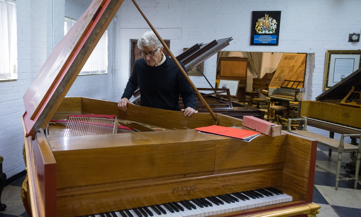 Royal piano restorer David Winston poses for a photograph with an exceptionally rare Pleyel grand piano at his workshop in Biddenden, south-east England on August 6. Photo: AFP