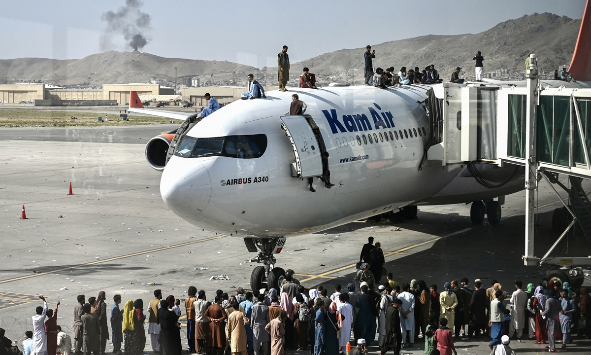 Afghan people climb atop a plane as they wait at the Kabul airport on Monday, after a stunningly swift end to Afghanistan's 20-year war. Photo: AFP