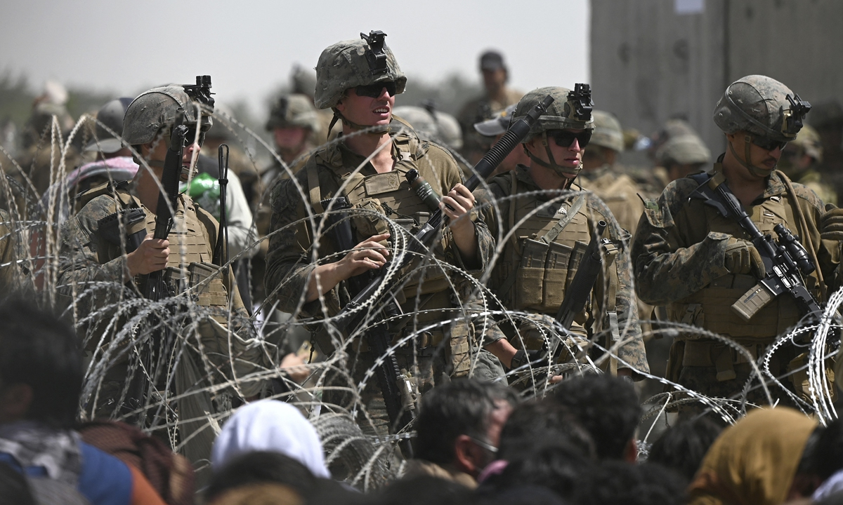 US soldiers stand guard behind barbed wire as Afghans sit on a roadside near the military part of the airport in Kabul on Friday, hoping to flee from the country. Photo: AFP