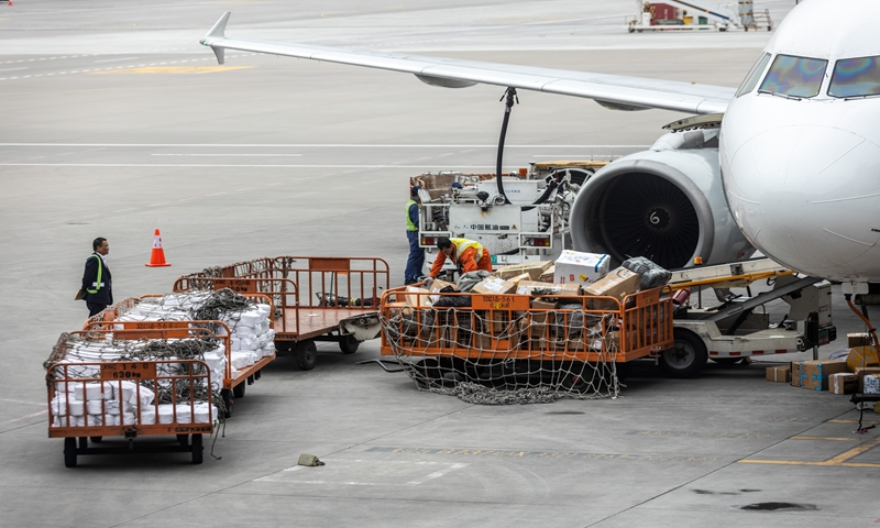 Employees load cargo onto a freight plane at Shanghai Pudong International Airport. File photo: VCG