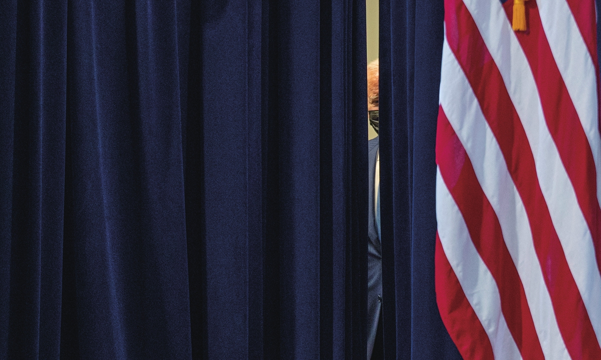 US President Joe Biden is seen through a curtain as he waits backstage before coming out to deliver remarks on the COVID-19 response and the vaccination program on August 23, in Washington, DC. Photo: AFP