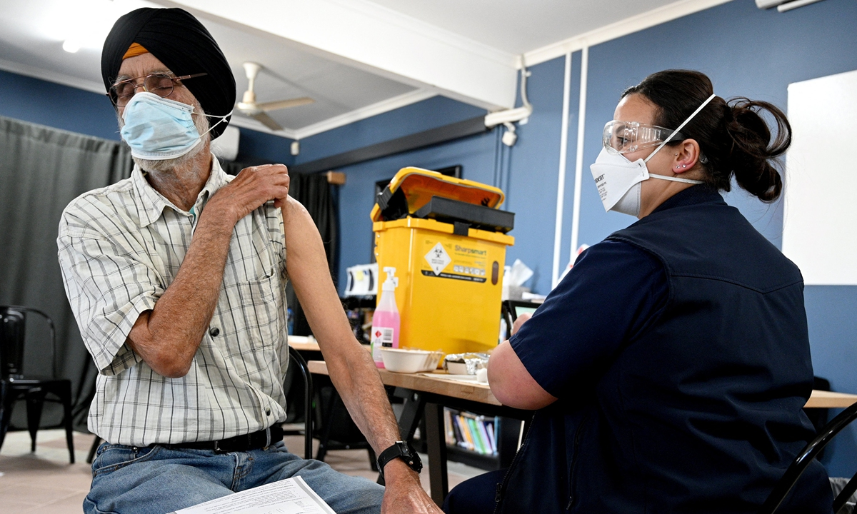 A man from a Sikh community gets ready to receive his first dose of Pfizer vaccine inside a temple in the suburb of Glenwood in Sydney, Australia on Thursday, as more than 1,000 new local coronavirus cases were reported for the first time during the pandemic. Photo: AFP